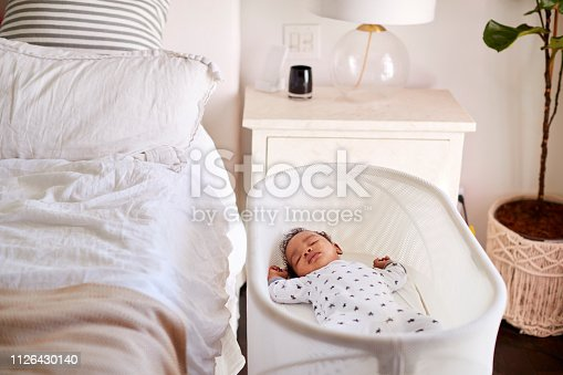 Three month old baby asleep in his cot beside the bed in his motherâ
