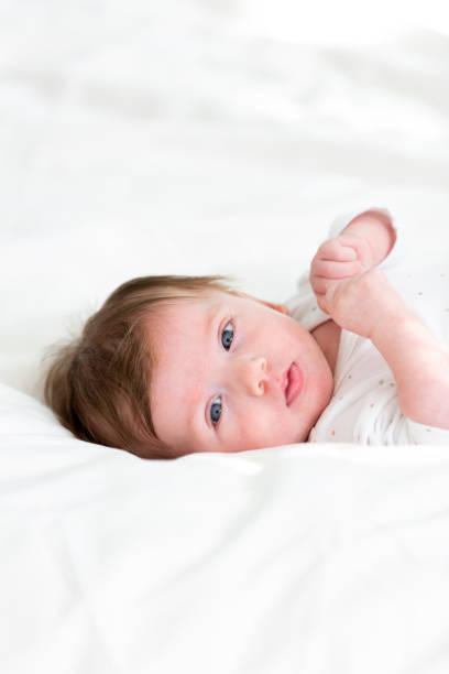 drei Monate alten, niedlichen Baby mit gepunkteten Körper ist im Bett liegend. – Foto