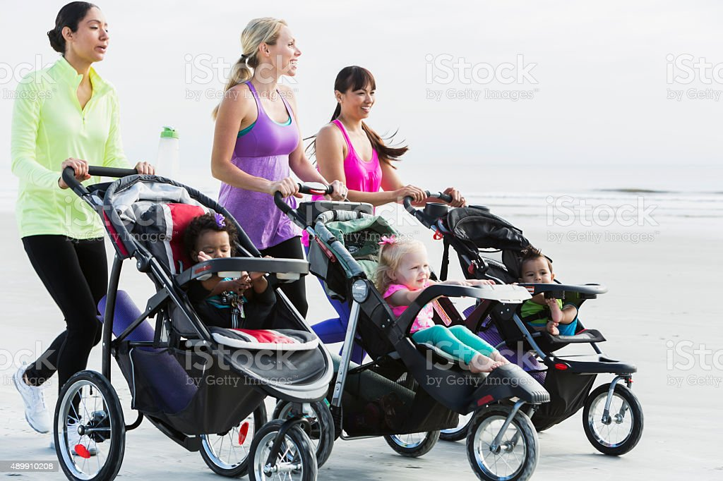 Three mothers and babies in strollers jogging on beach stock photo