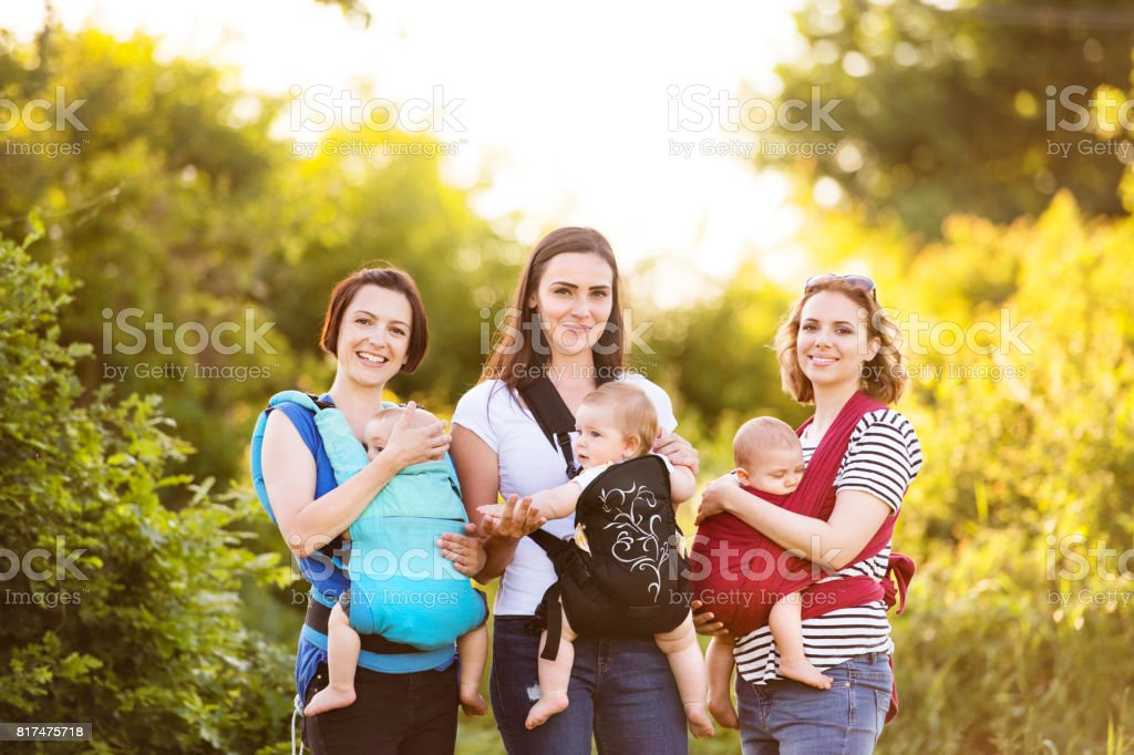 Three mothers on a walk in green nature, their children in baby carriers stock photo