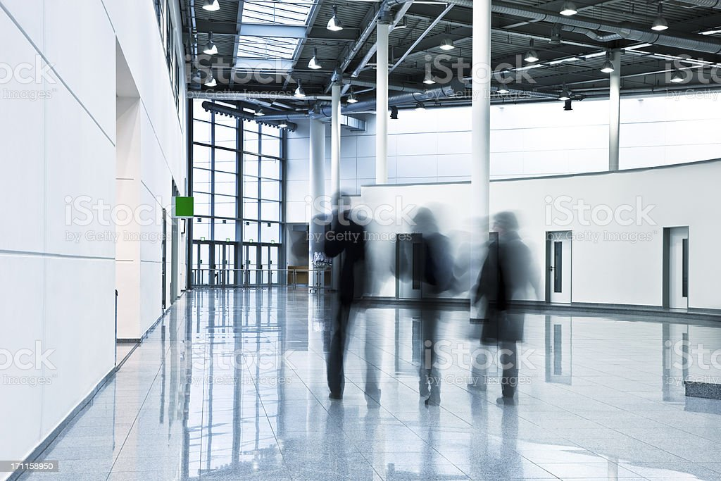 Three motion blurred business people walking in modern interior royalty-free stock photo