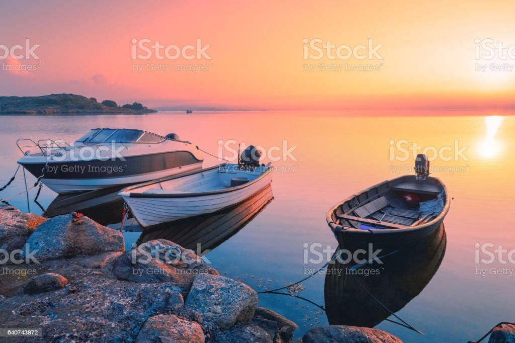 Three motor fishing boats at the pier on North Sea, Sweden coast line. Sunrise scenery. stock photo