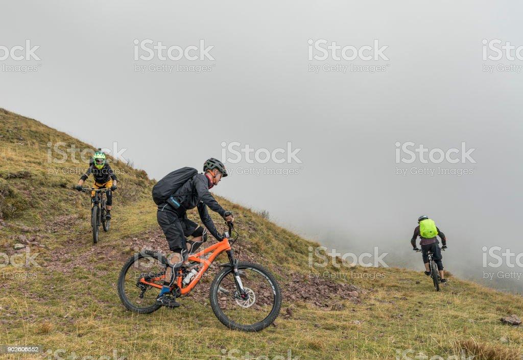 Three mountainbikers taking a hairpin turn in the Friulian Mountains, Italy. stock photo