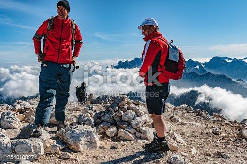 Three mountaineers on the top of Slovenian mountain Mangart; not far from Italian border,Primorska,Slovenia, Julian Alps, Europe.,Nikon D3x