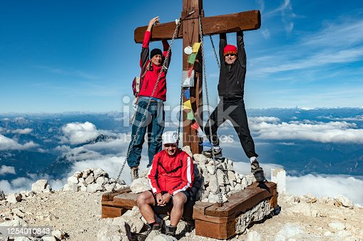 Three mountaineers on the top of Slovenian mountain Mangart; not far from Italian border,Primorska,Slovenia, Julian Alps, Europe.,Nikon D3x