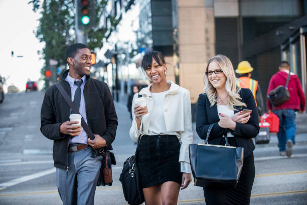three multi ethnic millennials in business attire with coffee in downtown los angeles - millennials stock photos and pictures