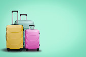 Three multi-colored plastic suitcases on wheels on a green background. Travel concept, vacation trip, visit to relatives.