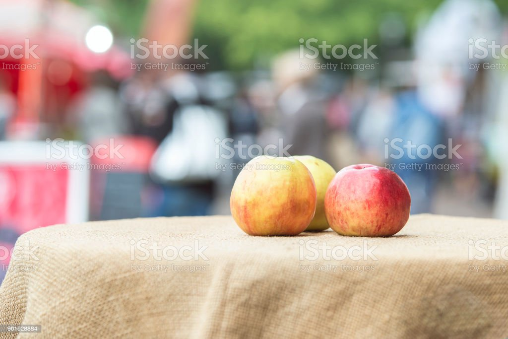 Three multi-colored ripe apples lie on a textured tablecloth as a symbol of the harvest at the festival. stock photo