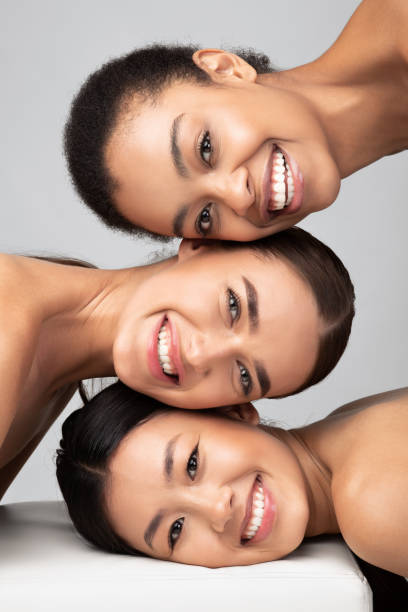Three Multicultural Ladies Posing Over Gray Background, Beauty Portrait, Vertical stock photo