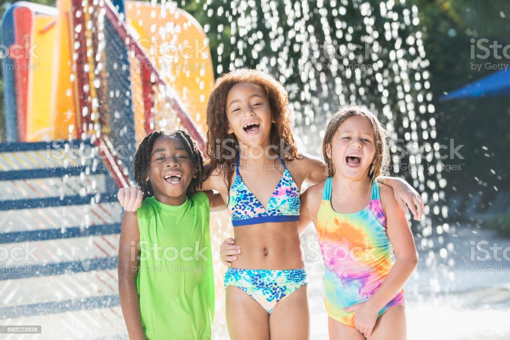 Three multi-ethnic children at a water park stock photo