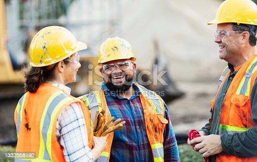 istock Three multi-ethnic construction workers chatting 1332558192