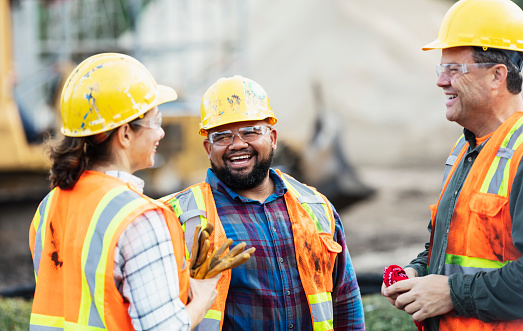 A group of three multi-ethnic workers at a construction site wearing hard hats, safety glasses and reflective clothing, smiling and conversing. The main focus is on the mixed race African-American and Pacific Islander man in the middle. The other two construction workers, including the woman, are Hispanic.