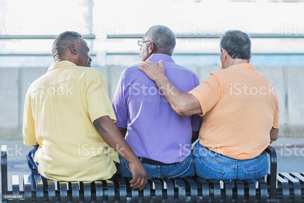 Three multi-ethnic senior men sitting on bench stock photo