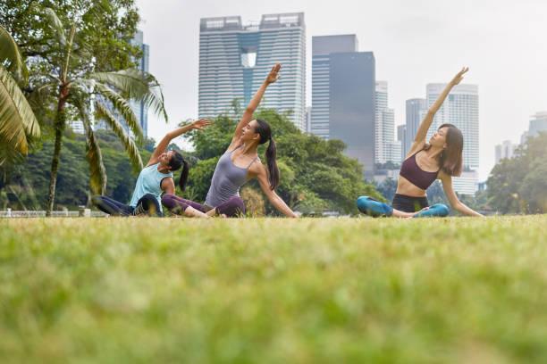 Three multi-ethnic women practising yoga outdoors in the city park stock photo