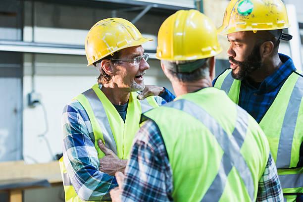 three multi-ethnic workers with safety vests and hard hats - obrero de la construcción fotografías e imágenes de stock