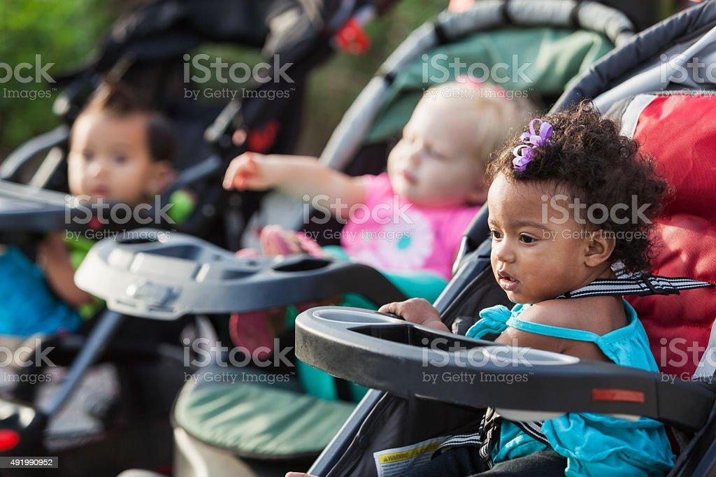 Tres bebés multirracial de bebé strollers - foto de stock