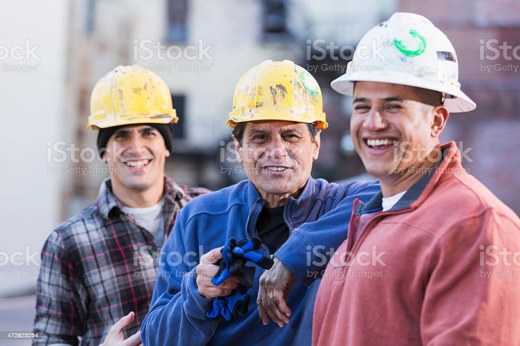 Three multiracial construction workers wearing hard hats stock photo