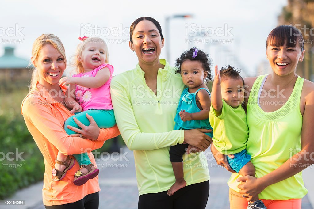 Three multi-racial mothers and their babies outdoors stock photo