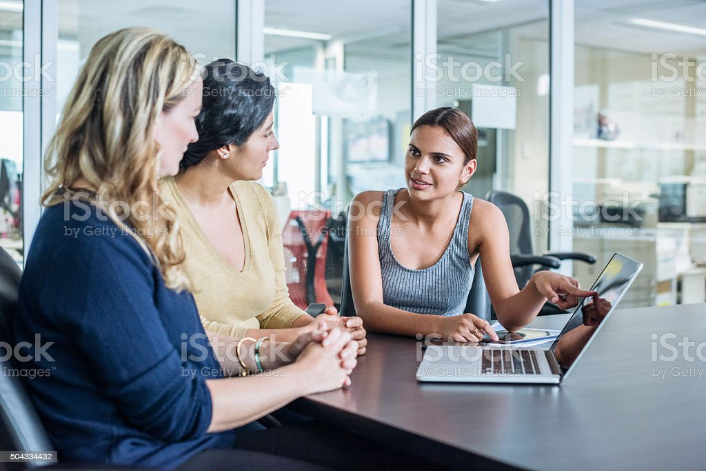 Three multiracial women using laptop computer in modern office stock photo