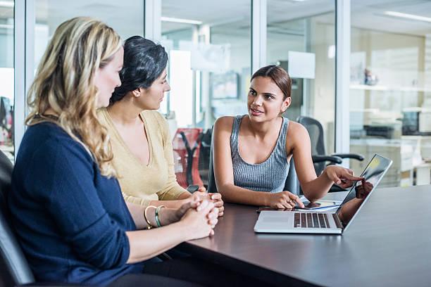 Three multiracial women using laptop computer in modern office stock photo