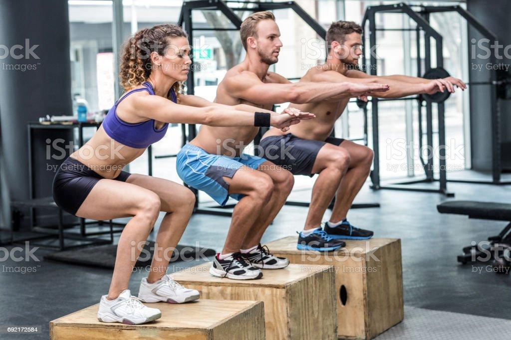 Three muscular athletes doing jumping squats stock photo
