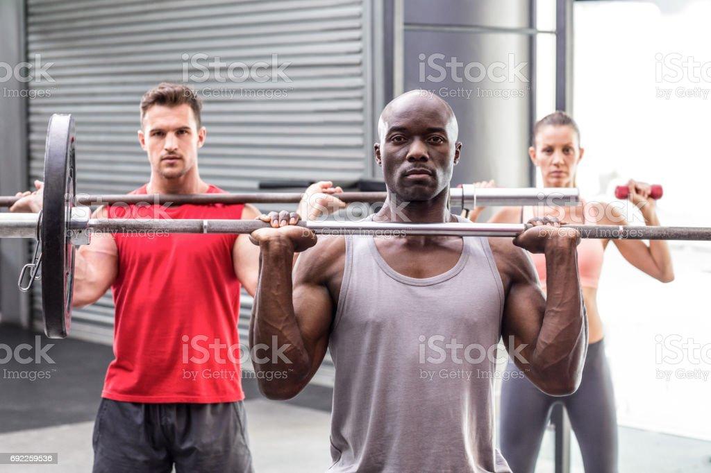 Three muscular athletes lifting barbells stock photo