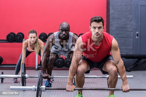 1069872470istockphoto Three muscular athletes lifting barbells 692259784