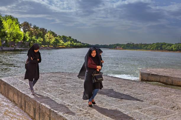 Trois femmes musulmanes sont promènent le long du fleuve, à Ispahan, en Iran. - Photo