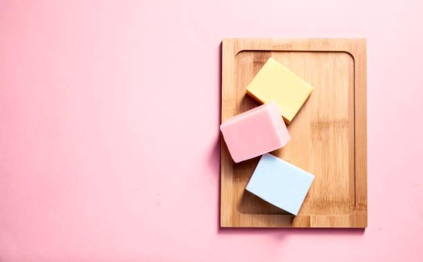 three natural soaps on a wooden desk - saponetta foto e immagini stock