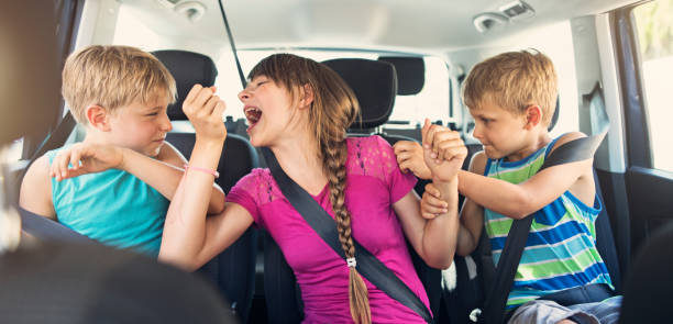 three naughty kids fighting in a car - fighting stock photos and pictures