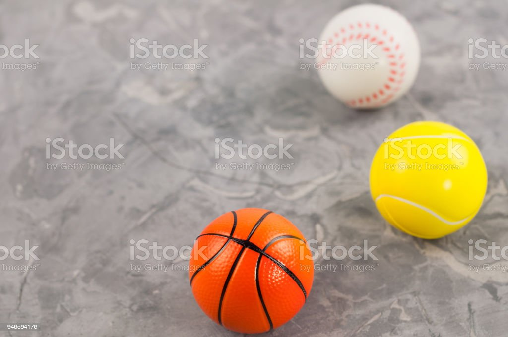 Three new soft rubber baseball and basketball and tennis balls on old...