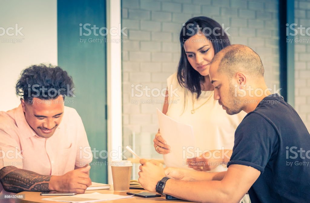Three New Zealand business people during a work meeting in an office environment. - Royalty-free Adult Stock Photo