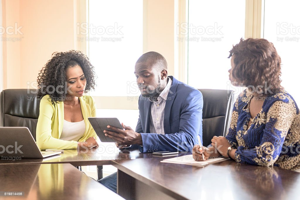 Three Nigerian colleagues in business meeting with tablet stock photo