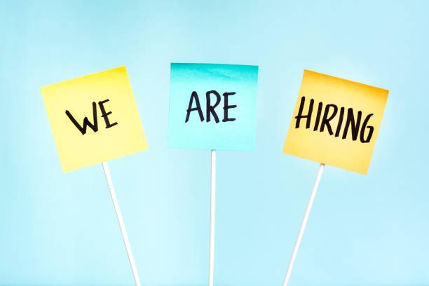 """tre noter med texten """"vi anställer"""" på plank hållaren. anställnings begrepp, sök jobb och rekryterings process. - new job bildbanksfoton och bilder"""