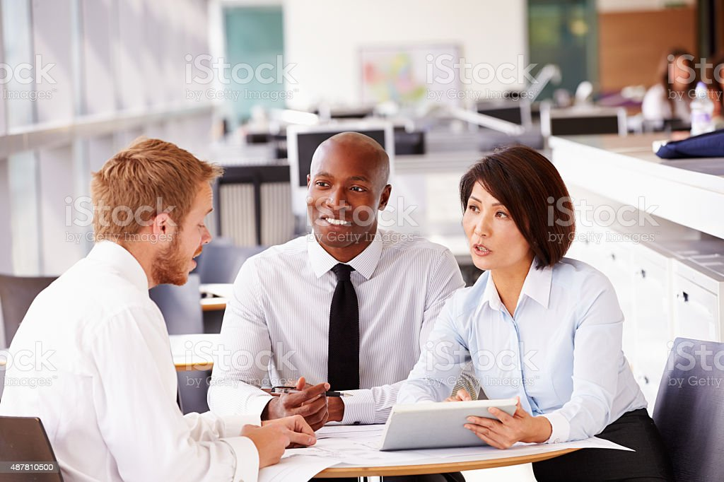 Three office colleagues in a casual team meeting stock photo