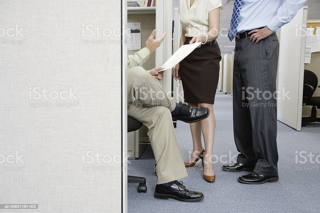 Three office colleagues standing by cubical, low section foto de stock royalty-free