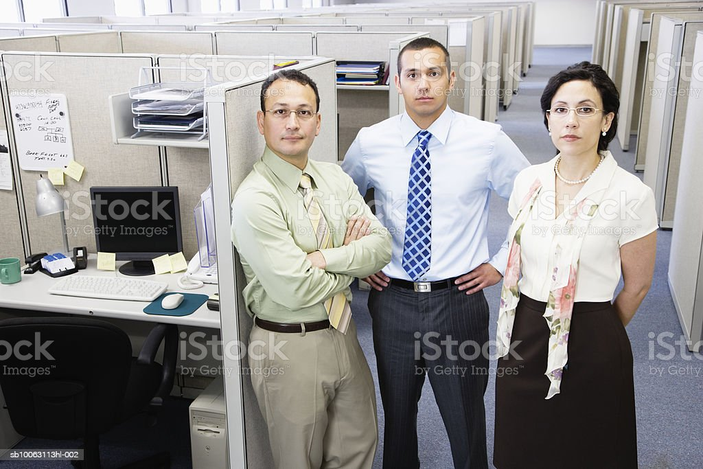 Three office colleagues standing by cubical, portrait foto de stock libre de derechos