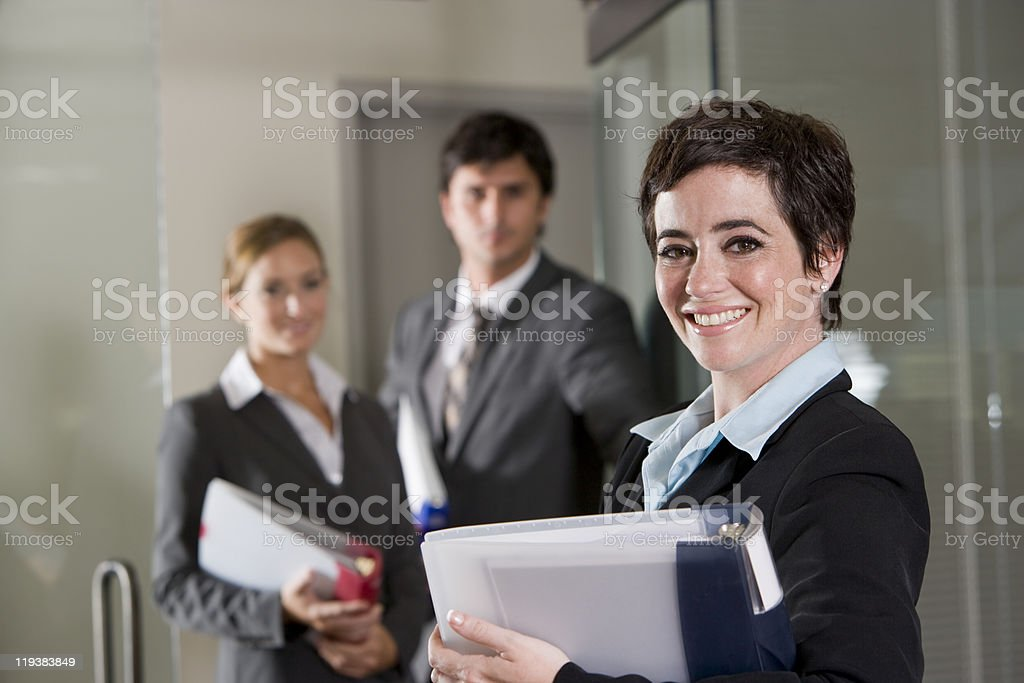 Three office workers at door of boardroom royalty-free stock photo