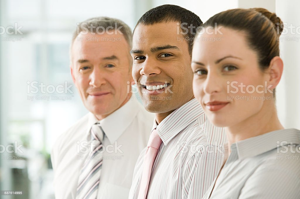 Three office workers in a row stock photo