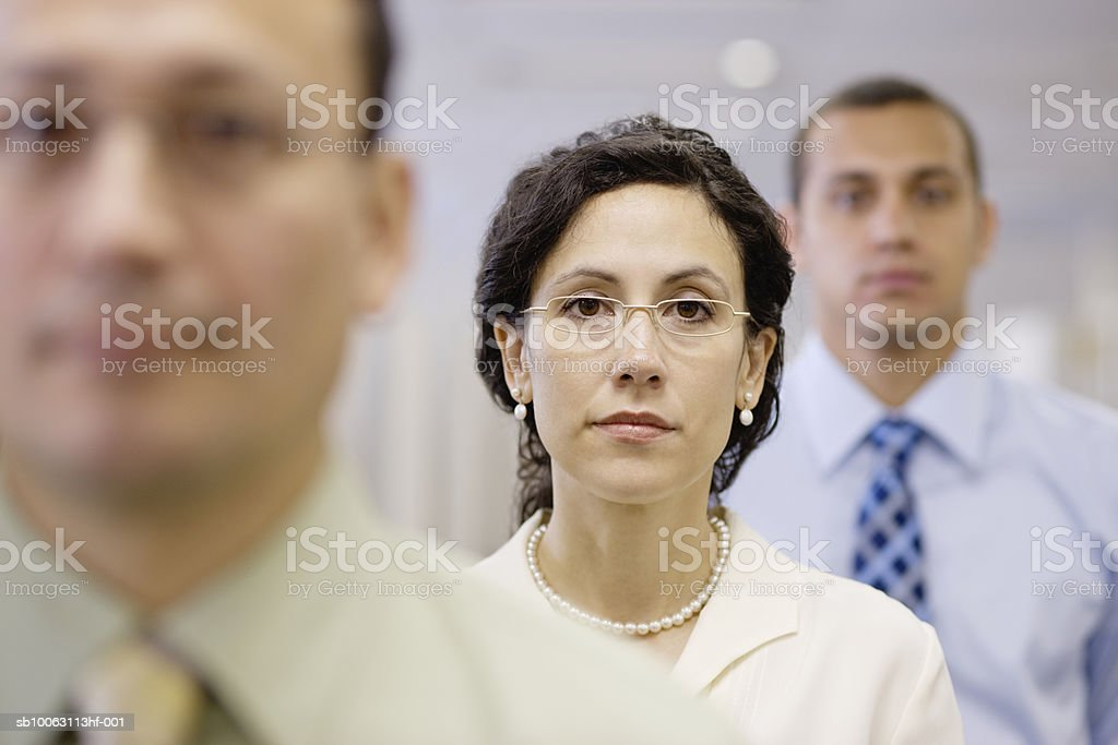 Three office workers standing in row, focus on woman in middle royalty-free stock photo
