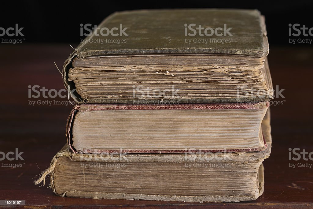 Three old books on an old table stock photo