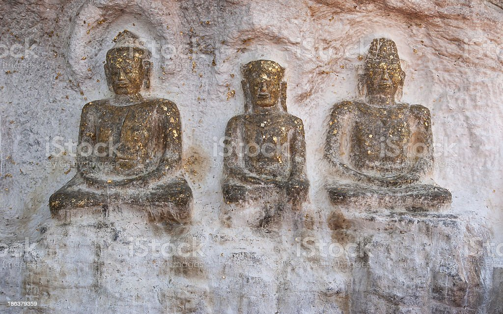 Three old buddha image on the rock royalty-free stock photo