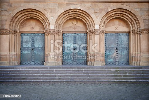 High-res photograph of weathered metal church doors and steps.