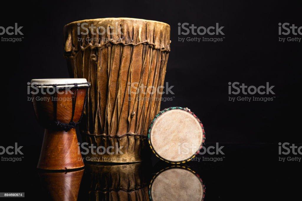 Three old handmade Djembe drums isolated on black stock photo