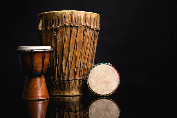 Three old handmade Djembe drums isolated on black stock photo