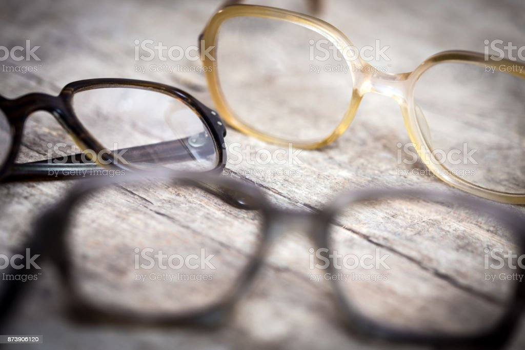 three old nerdy hornrims or eye glasses on wooden table stock photo