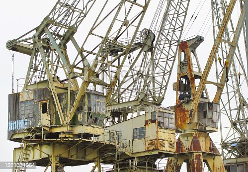 Three old, rusty cranes in a row in the harbor. Photo was made in the harbor of Antwerp, Belgium