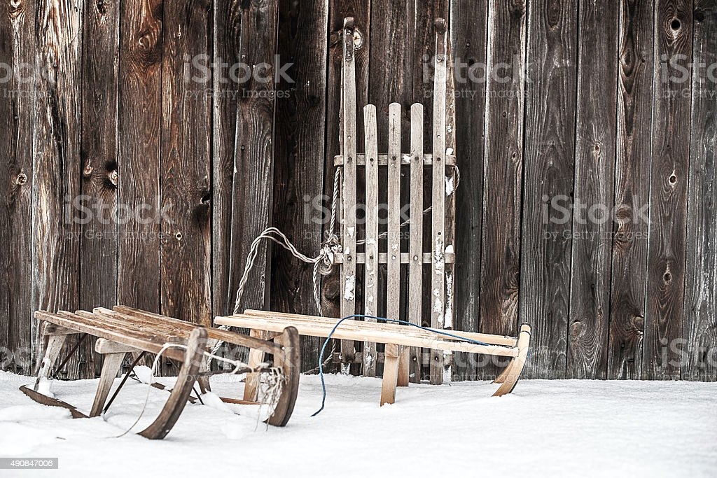 three old sleighs on wooden wall stock photo