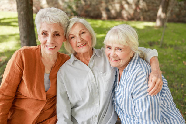 Three old women looking at camera and smiling stock photo