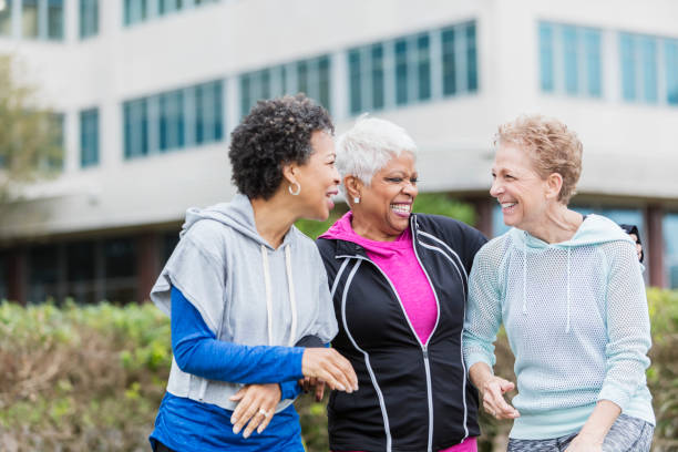 Three older multi-ethnic women hanging out together stock photo